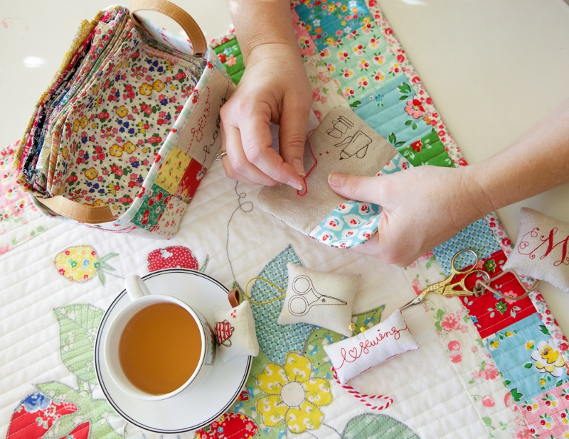 hand sewing and drinking tea