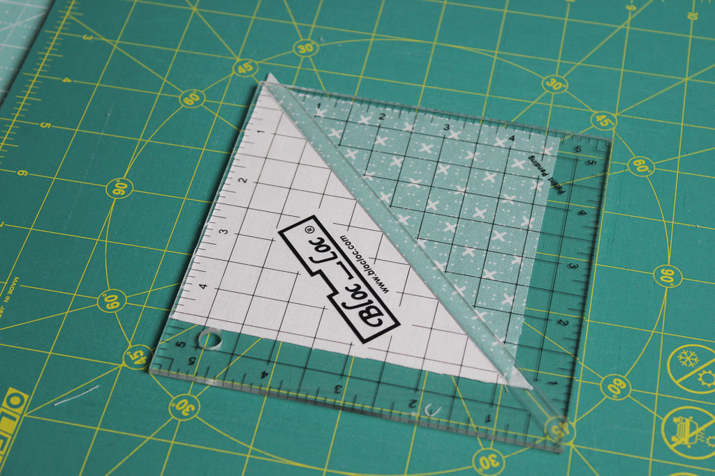 Using a BlocLoc ruler to trim half square triangles